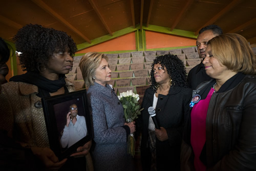 Sec. Clinton spoke with mothers who lost children to gun violence in Chicago. In the background are markers with the name and age of some of the victims lost to gun violence.