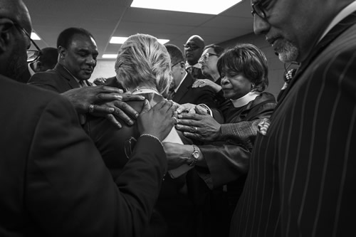 Sec. Clinton prays with members of the Olivet Institutional Baptist Church prior to addressing the Community Coalition in Cleveland, Ohio.