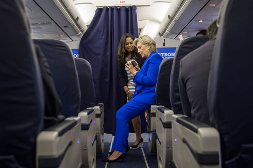 Sec. Clinton checks out iPhone photos of Maya Harris' new granddaughter on September 8, 2016 during a flight on the Stronger Together campaign plane. Both women had recently become grandmothers - Hillary for the second time and Maya for the first.